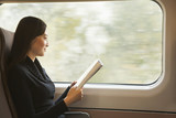 Young Woman Reading a Magazine While Riding the Train