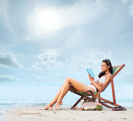 Young, beautiful, sporty and sexy woman reading on the beach