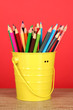 Colorful pencils in pail on table on red background