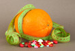 Orange with measuring tape and multicolor pills,