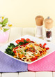 Noodles with vegetables in plate on wooden table