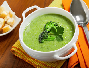 Broccoli cream soup and crusts on a table