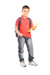 Full length portrait of a schoolboy with backpack holding a note
