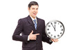 A young man in suit pointing on a clock