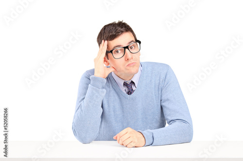 Doubtful guy sitting and thinking on a table