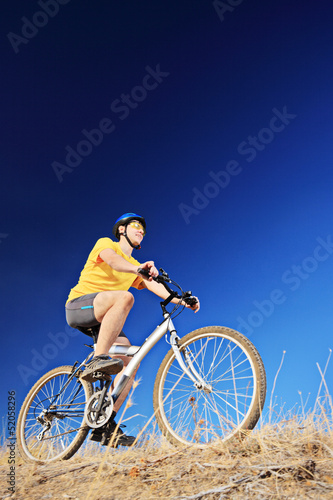 A young male wearing yellow shirt and helmet on a bike