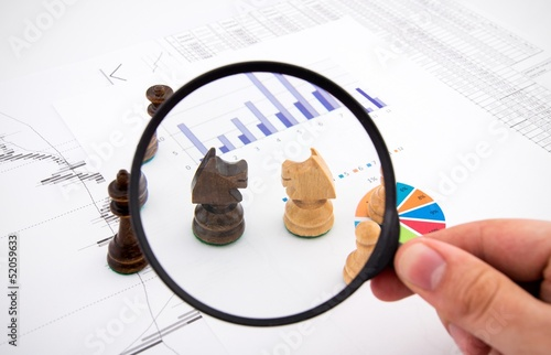 Business concept with magnifier and chess pieces on colorful bac
