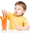 Little boy is eating carrot