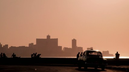 People, Caribbean sea and skyline of Havana, Cuba, at sunset