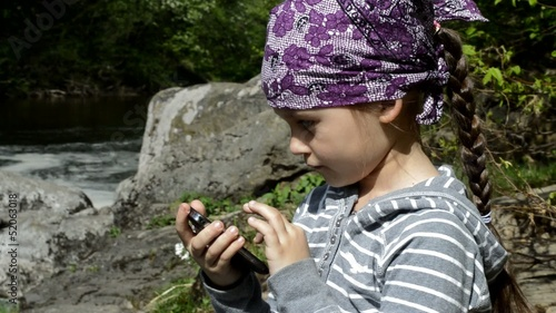 girl playing on the smart phone near the river
