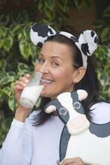 Happy funny mature woman drinkign milk
