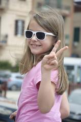 "Smiling Little Girl With Sunglass Doing ""V"""