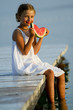 Summer  - girl eating fresh watermelon on the pier