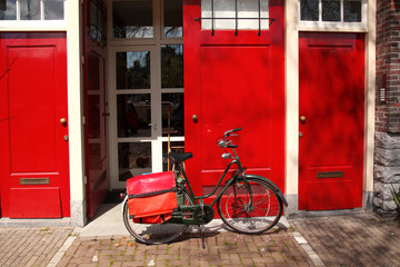 Bicycle against red house in Amsterdam, Holland