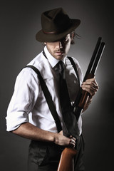 Handsome gangster posing with shotgun and hat