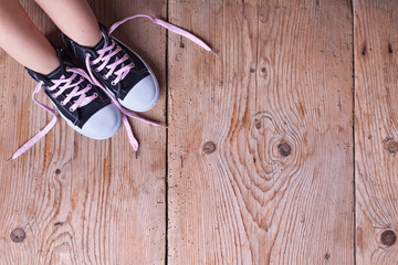 Child feet in sneekers on old wooden floor