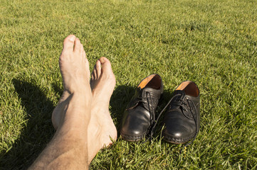 feet relaxing in the grass with his shoes