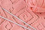 A fragment of a knitted blankets, pink skein of yarn