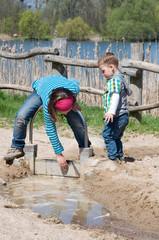 Kinder spielen mit Wasser am Strand