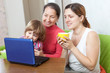 Happy women  of three generations with netbook