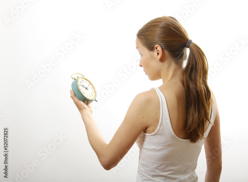 woman looking at alarm clock, on white background