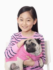 Portrait of girl holding pet pug