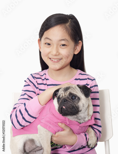 Portrait of girl holding pet pug