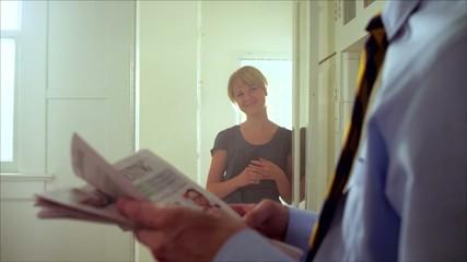 молодой мужчина с газетой со своей супругой