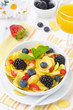 Cornflakes, fresh berries, orange juice for breakfast vertical