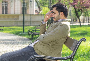 Headache, tiered man sitting in a park on bench