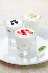 three yogurt with fruit in a glass beaker vertical