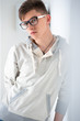 Portrait of young fashionable man leaning on white wall and wear