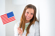 Portrait of a lovely young woman with United State's flag smilin