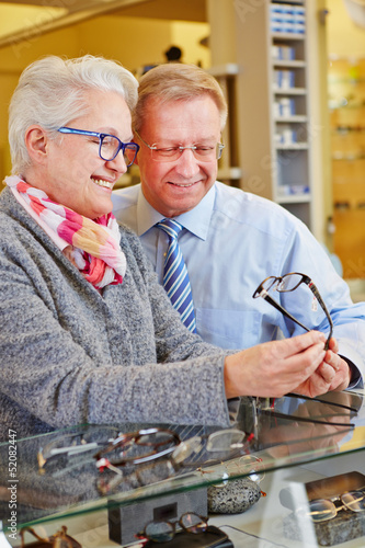 Two seniors buying glasses at optician