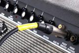 black guitar amplifier with yellow cord
