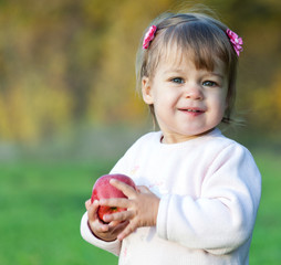 Baby girl in the park holding red apple