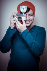 young stylish man holding old camera