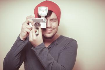 young stylish man holding old camera