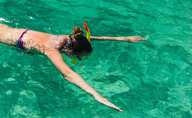 Girl swimming in the  sea with a mask and snorkel