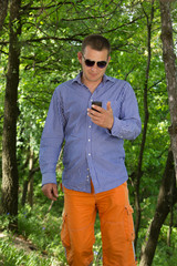 Young man using phone while walking through the green forest
