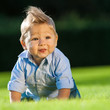 happy little boy playing on grass in the park
