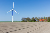 Big wind turbine in Dutch Farmland with farmhouse
