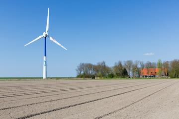 Big wind turbine in Dutch Farmland with farmhouse