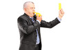 A mature businessman blowing a whistle and showing a yellow card