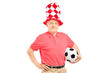 A middle aged male fan with hat holding a soccer ball