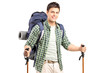 A smiling hiker with backpack and hiking poles posing