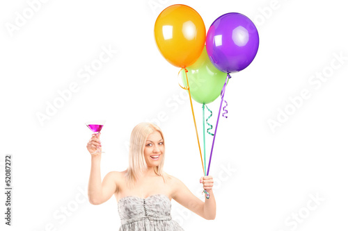 A pretty blond female holding balloons and cocktail