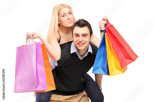 A young man giving a piggyback ride to a woman with shopping bag
