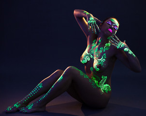 Elegant woman with green UV pattern on body