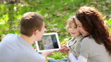 Happy family using tablet PC outdoors in autumn park